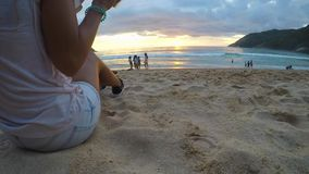 Young Woman`s Hand Takes A Cup Of Iced Coffee, makes a Sip And Puts It Back on sand. Beach sunset, Gopro
