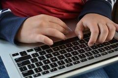 Millennial woman using a laptop computer, close up stock photography