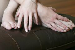 Young woman's Hands and feet. Woman's bare feet and hands on a leather cushion royalty free stock photography