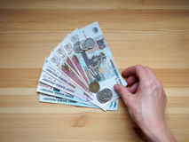 Young woman`s hands is holding rubles on wooden table. Young girl`s hands is holding rubles on wooden table Stock Image