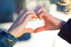 A young woman's hands making a heart shape Stock Photos