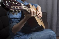Young woman`s hands playing a acoustic classic guitar stock image