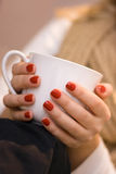 Young woman's hands with red nail polish holding a white cup. A cup of coffe. A blond woman with a cup of tea and beige scarf Royalty Free Stock Image