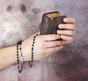 Young woman's hands with a rosary and a bible Stock Photo