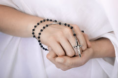 Young woman's hands with a rosary Stock Photo