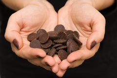 Young woman's hands in a shape of heart with dark chocolate. Stock Images