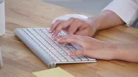Young woman`s hands typing at computer keyboard stock footage