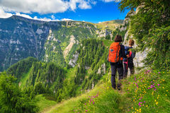 Young woman's hikers walking in mountains,Bucegi,Carpathians,Transylvania,Romania. Woman's hiking team with colorful backpacks walking on narrow trail,Bucegi royalty free stock photography
