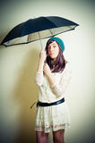 Young woman in 70s hippie style posing with umbrella Stock Images