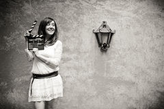 Young woman in 70s hippie style smiling with clapperboard black Stock Images