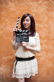Young woman in 70s hippie style smiling with clapperboard Stock Images