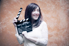 Young woman in 70s hippie style smiling with clapperboard Stock Photo