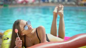 Young woman 20s laying and relaxed near pool at summer holiday. Bikini girl sunbathing lying on inflatable mattresses. Happy teenager enjoying summer vacation stock video