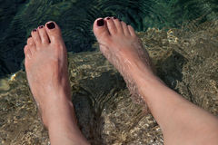 Young woman's manicured feet in water Royalty Free Stock Image