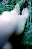 Young Woman's Out Of Focus Legs. Out of focus closeup of a young woman's legs.  Foot is in focus.  Playing in a field.  Glow and blue tone added Stock Photography