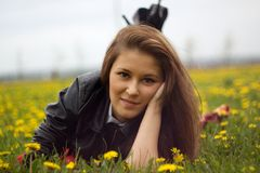 A young woman's portrait close up. A young woman laying on the grass with yellow dandelions facing camera with a calm expression Stock Photography