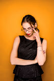 The young woman`s portrait with wary emotions. On orange studio background Royalty Free Stock Photo