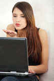 Young woman's sending kiss to laptop. Royalty Free Stock Photo