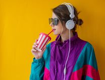 Young woman in 90s style clothes with cup and headphones stock photography