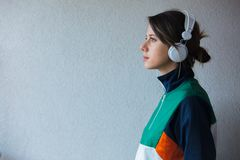 Young woman in 90s style clothes with headphones stock photo