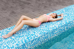 Young woman in s swimsuit. Girl relaxing in a pool Royalty Free Stock Photo
