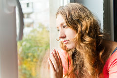 Young woman is sad at the window Royalty Free Stock Photo
