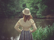 Young woman with safari hat by pond in forest. A young woman wearing a safari hat is standing by a pond in the forest on a sunny summer day royalty free stock photography