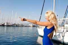 Young woman on sailing holidays pointing with her forefinger. Royalty Free Stock Images
