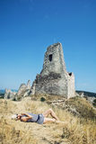 Young woman in a sailor outfit lying on the dry grass and behind. Is the castle Cachtice. Tourism, fashion and ruins Stock Photos