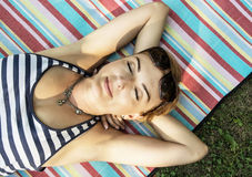 Young woman in sailor outfit is lying on the retro blanket with Royalty Free Stock Images