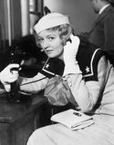 Young woman in a sailors uniform on the telephone Stock Photo
