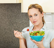 Young woman with salad. Pretty young woman standing in the kitchen and holding a bowl with salad Royalty Free Stock Photography