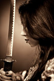 Young woman with samurai sword. Sepia color Royalty Free Stock Photos