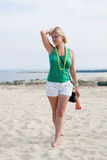 Young woman on a sand dune. Young woman standing on a big sand dune holding her shoes Stock Image