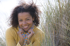 Young woman on sand dune, smiling, portrait Royalty Free Stock Photography