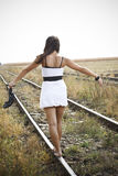 Young woman with sandal in hand on the railway Royalty Free Stock Image