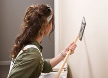 Young woman is sanding wall with pole sander before painting. In house under remodeling Royalty Free Stock Photos