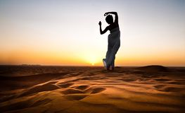 Young woman in sandy desert. At sunset Royalty Free Stock Image