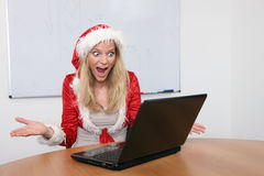 Young woman in Santa´s costume with laptop Royalty Free Stock Images