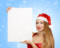 Young woman in santa claus hat with christmas card. Beautiful young woman in christmas suit holding greeting card or advertisement on blue background with Stock Images