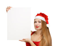 Young woman in santa claus hat with christmas card. Beautiful young woman in christmas suit holding greeting card or advertisement isolated on white background Stock Photos