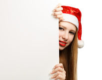 Young woman in santa claus hat with christmas card. Beautiful young woman in christmas suit holding greeting card or advertisement isolated on white background Stock Image