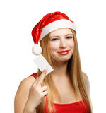 Young woman in santa claus hat with christmas card. Beautiful young woman in christmas suit holding greeting card or advertisement isolated on white background Royalty Free Stock Photo