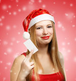 Young woman in santa claus hat with christmas card. Beautiful young woman in christmas suit holding greeting card or advertisement on red background with falling Royalty Free Stock Photography