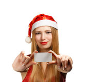 Young woman in santa claus hat with christmas greeting card. Beautiful young woman in christmas suit holding greeting card or advertisement isolated on white Royalty Free Stock Images