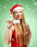 Young woman in santa claus hat with christmas invitation card. Beautiful young woman in christmas suit holding greeting card or advertisement on green background Royalty Free Stock Image