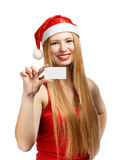Young woman in santa claus hat with christmas invitation card. Beautiful young woman in christmas suit holding greeting card or advertisement isolated on white Stock Photo