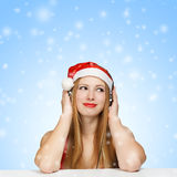 Young woman in santa claus hat and headphones on blue background. With falling snow Royalty Free Stock Photography