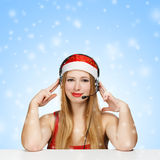 Young woman in santa claus hat and headphones on blue background. With falling snowflakes Stock Photo