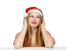Young woman in santa claus hat and headphones isolated on white. Background Stock Image